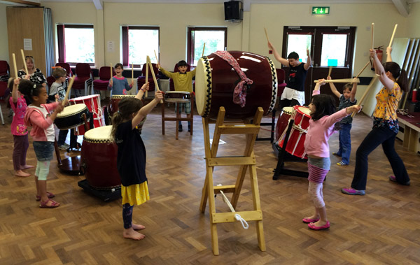 Children having fun while learning a simple taiko drumming piece.