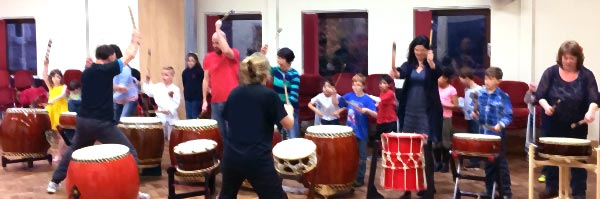 Children and adults having fun playing Taiko in a previous workshop.