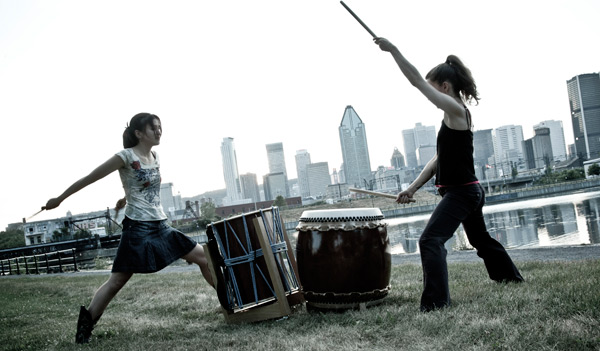 A picture of 2taiko playing by the river.